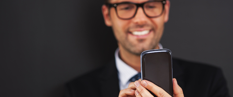 Man looking at his phone and smiling at his improved lead generation results