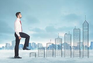 Business man climbing up on hand drawn buildings - why sales never get any easier