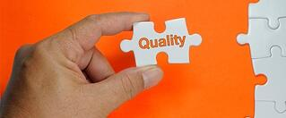 Hand holding jigsaw peice with the word 'quality' printed on the front