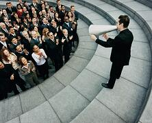 Man in suit with megaphone delivering speech to group of professionals